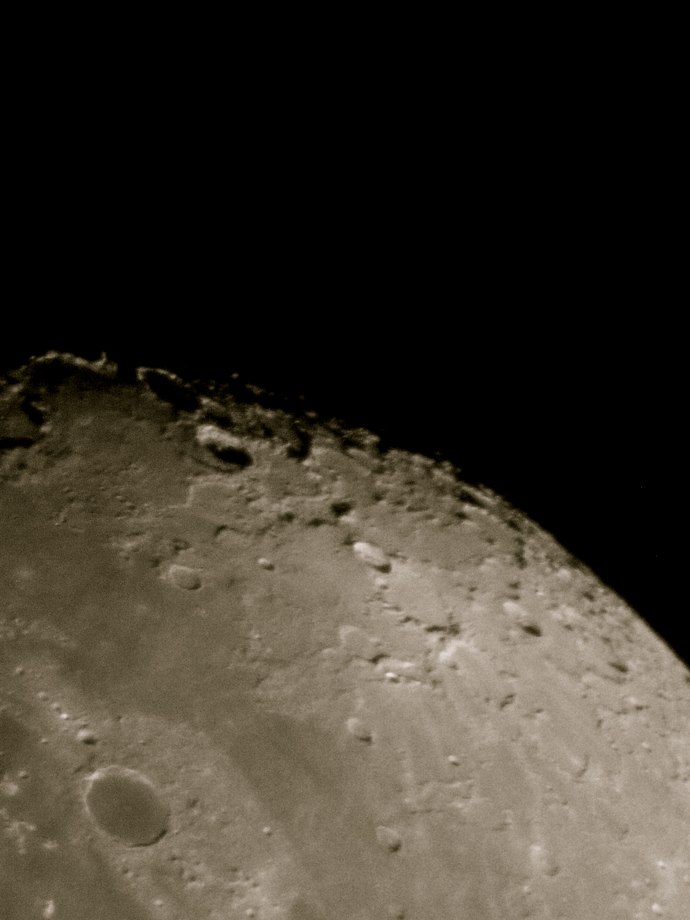 The north-central portion of the moon. The smooth dark crater on the lower left is Plato, and the deeply-shadowed crater with the bright rim far to the north is Philolaus.