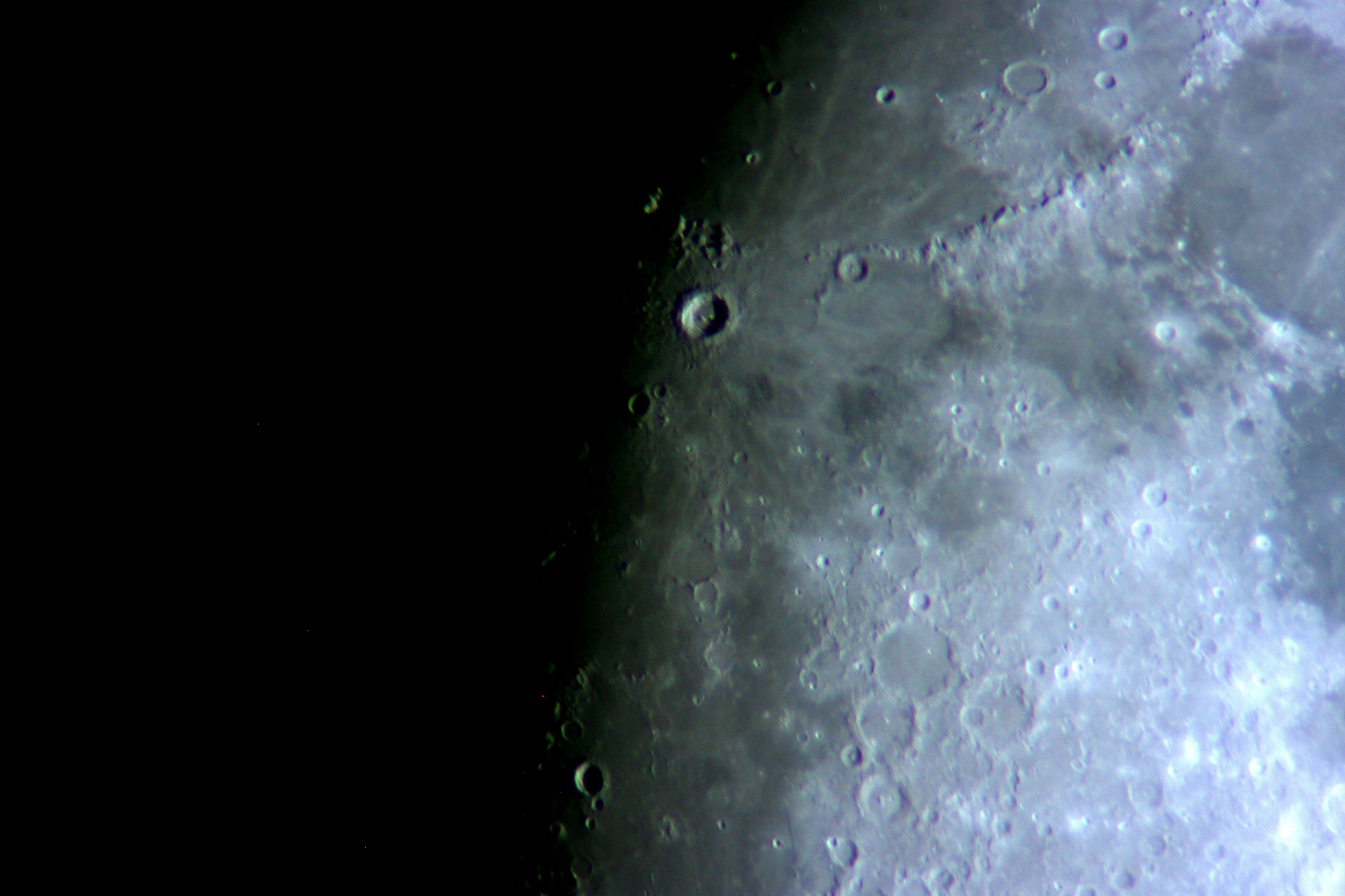 The prominent crater in the upper middle is Copernicus, with the Apennine mountains curving away to the northeast, marking the rim of Mare Imbrium, the Sea of Rains. Near the lower left are three craters making a backwards comma--these are Ptolemaeus, Alphonsus, and Arzachel (Arzachel has a prominent central peak).